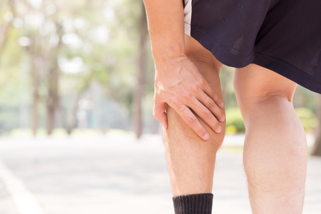 Person with calf pain holding calf muscle outdoors.