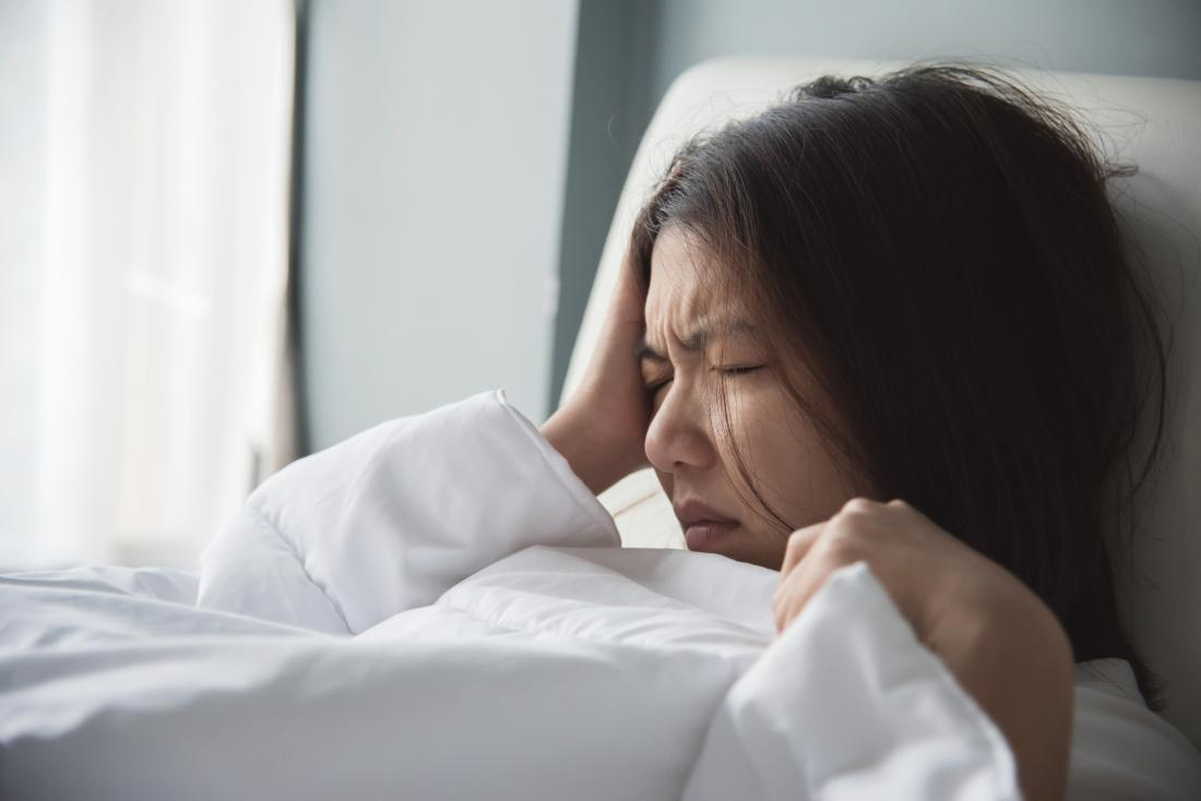 Woman with migraine in bed holding right side of head.