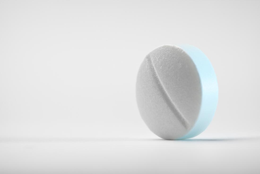 prednisone tablet, white round pill standing up on white background.