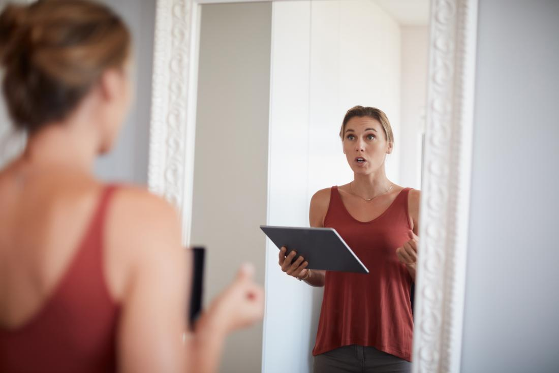 a woman practising talking in front of a mirror as that is How to stop stuttering