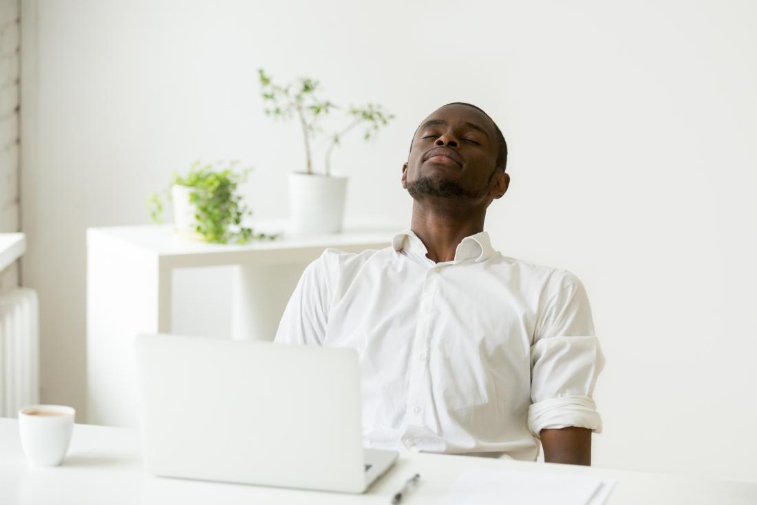 Man sitting at desk in minimalist office, doing deep breathing exercises.