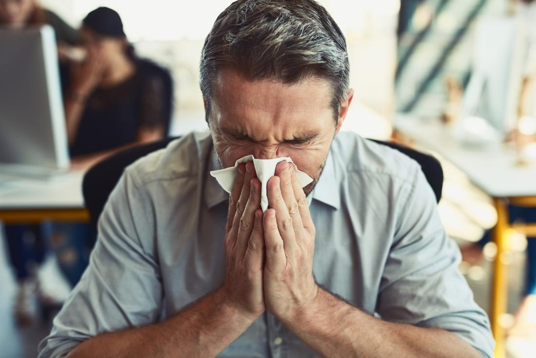 Man in office blowing nose in tissue.