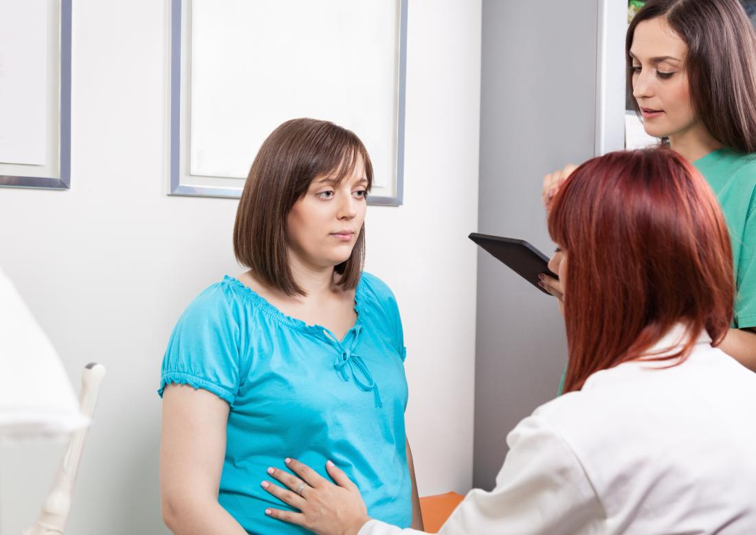 Pregnant woman having checkup with doctor.