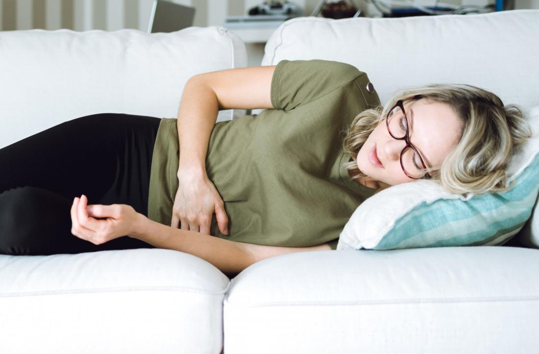 Woman with endometriosis lying on side holding stomach because of abdominal pain.