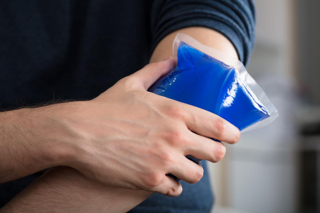 Person putting ice pack on skin around elbow