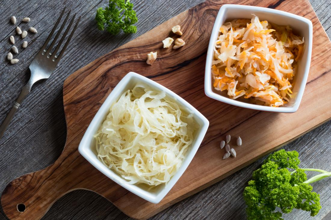 Fermented cabbage sauerkraut in two bowls on chopping board