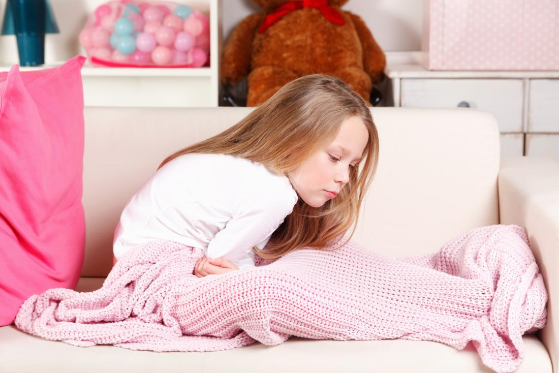 young girl with stomach ache sitting on sofa