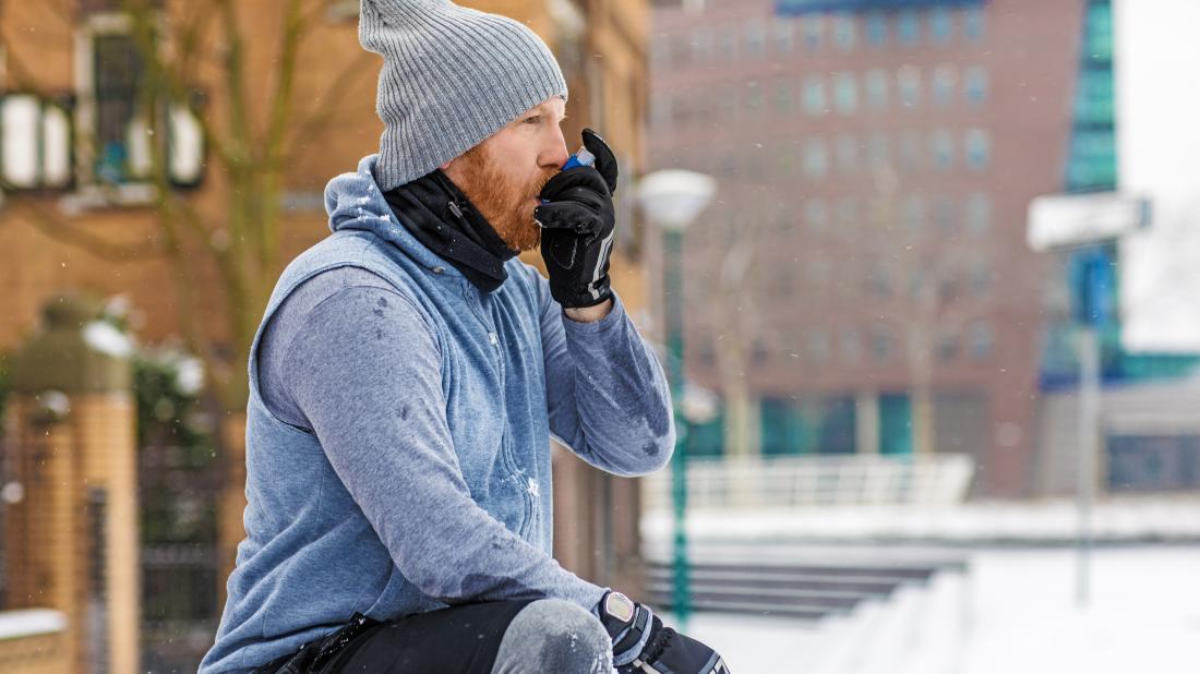 a man exercising outside and using an inhaler to treat his asthma