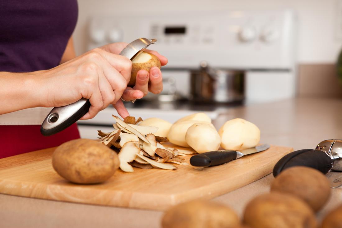 Person peeling potatoes