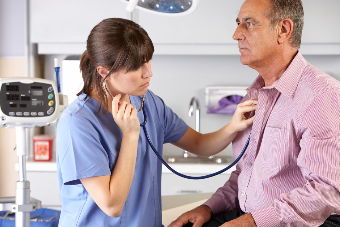 Female doctor using stethoscope to listen to breathing of senior male patient.
