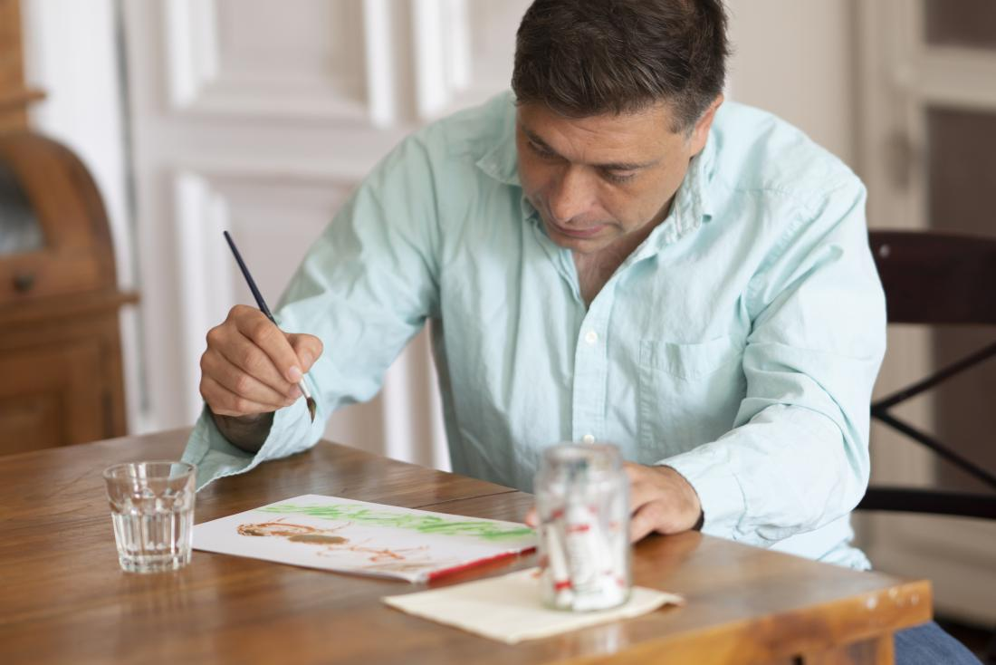 a man painting at table
