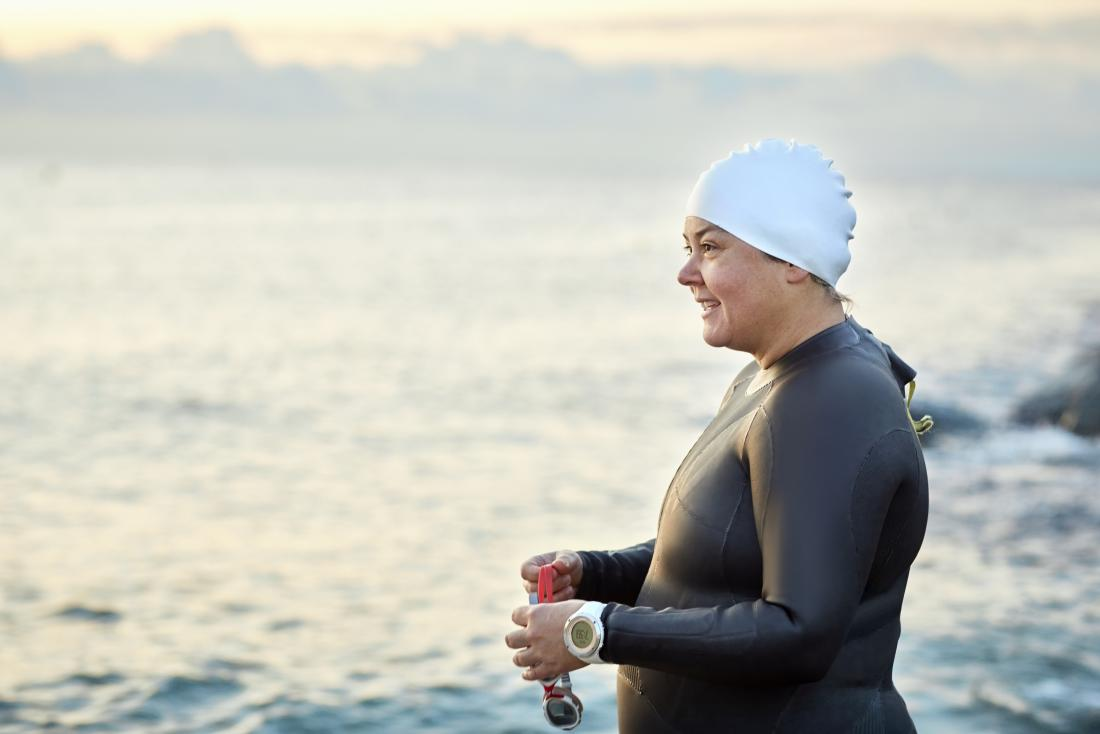 Woman athlete by the sea in outdoor swimmer wetsuit, going swimming.