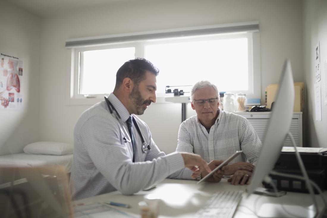 Доктор показывает буфер обмена пациенту в офисе, обсуждая нарушения иммунодефицита