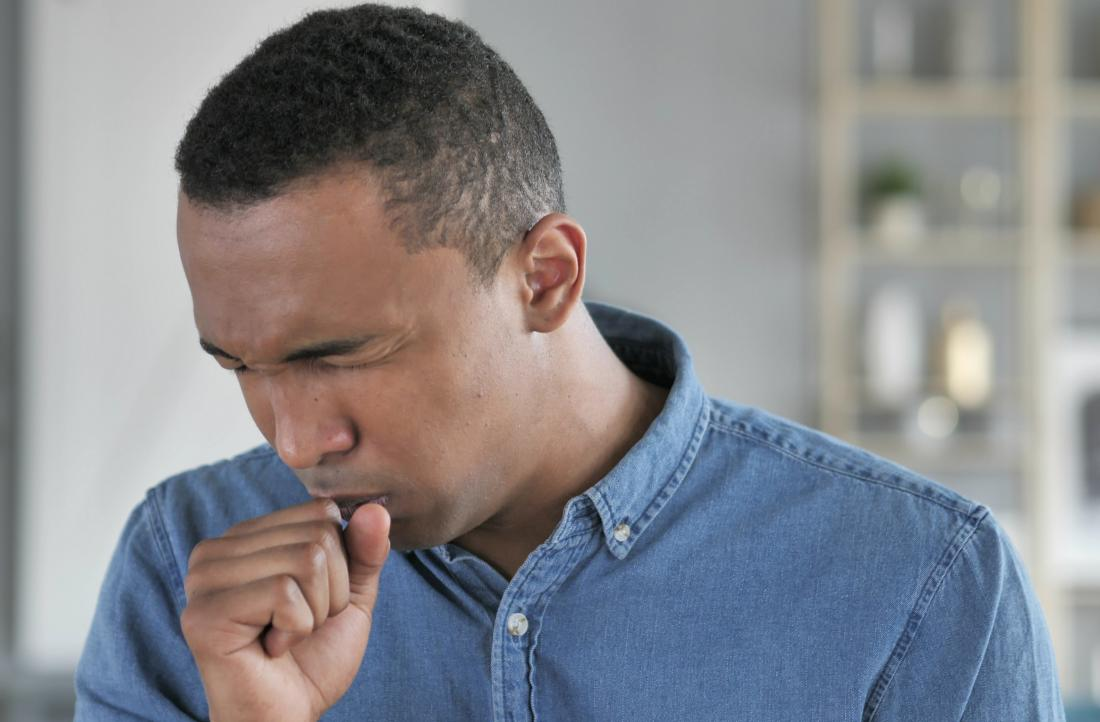 Man coughing into fist