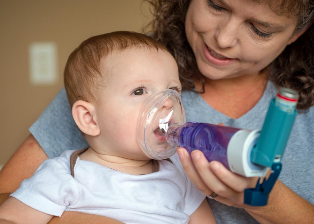 mother using an asthma inhaler with mask attachment on baby