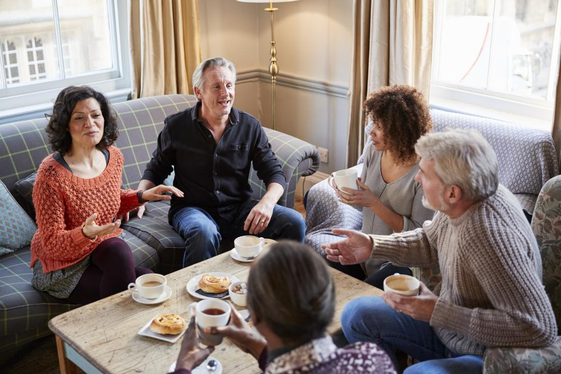 group of middle aged friends having coffee and pastries at home