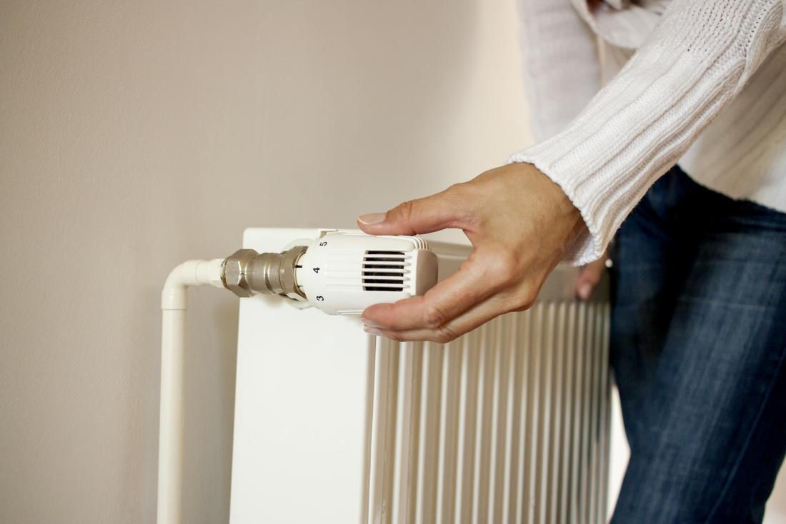 woman turning up radiator thermostat