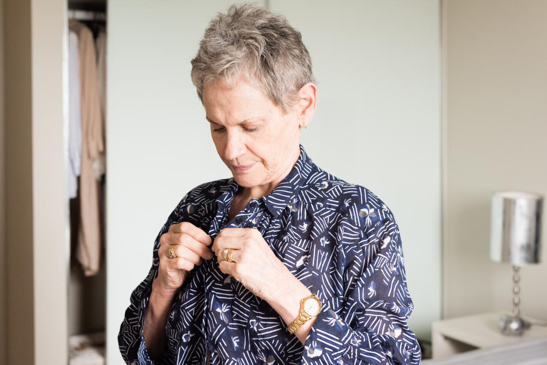 Senior or mature woman buttoning up shirt while getting dressed.