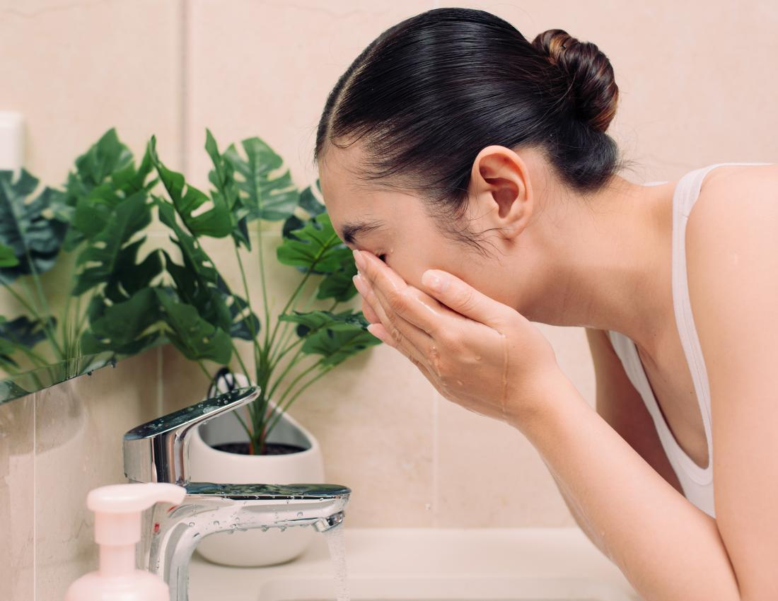 Woman washing her face with an exfoliator for dry skin on face