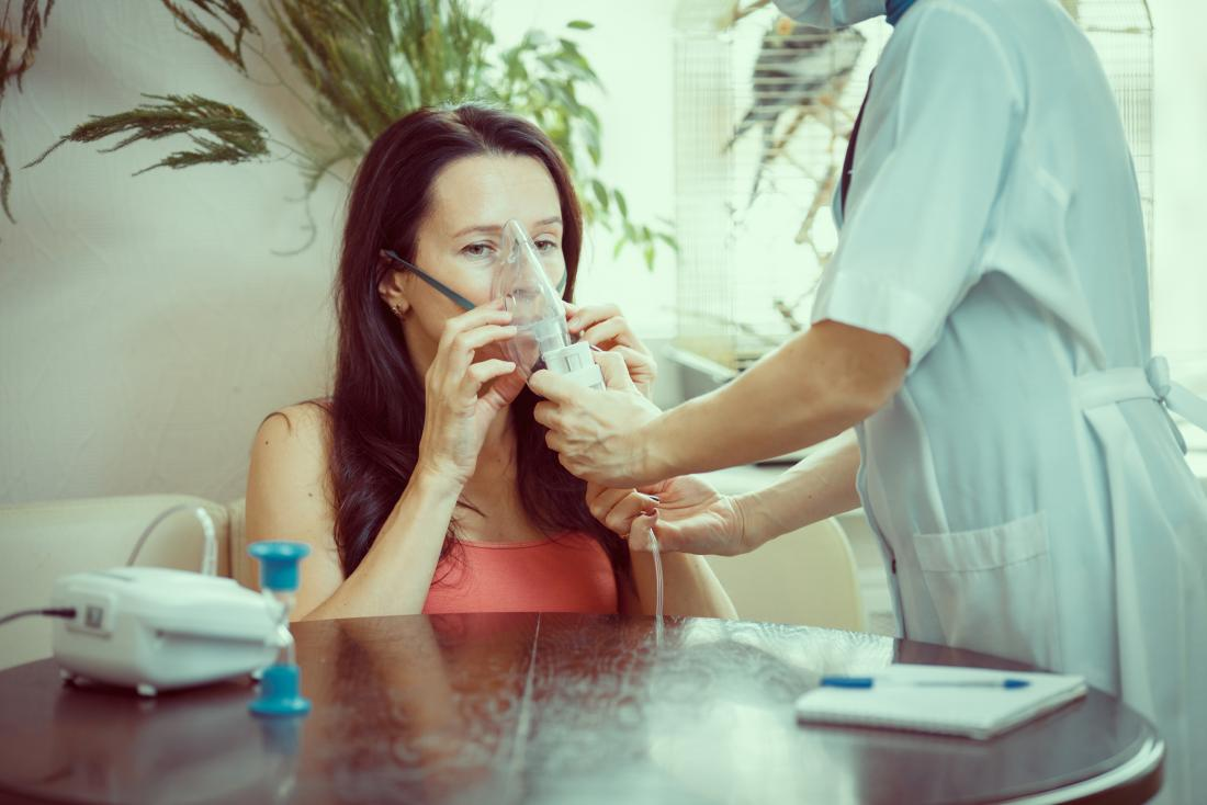 Healthcare professional helps woman with asthma use a nebulizer.