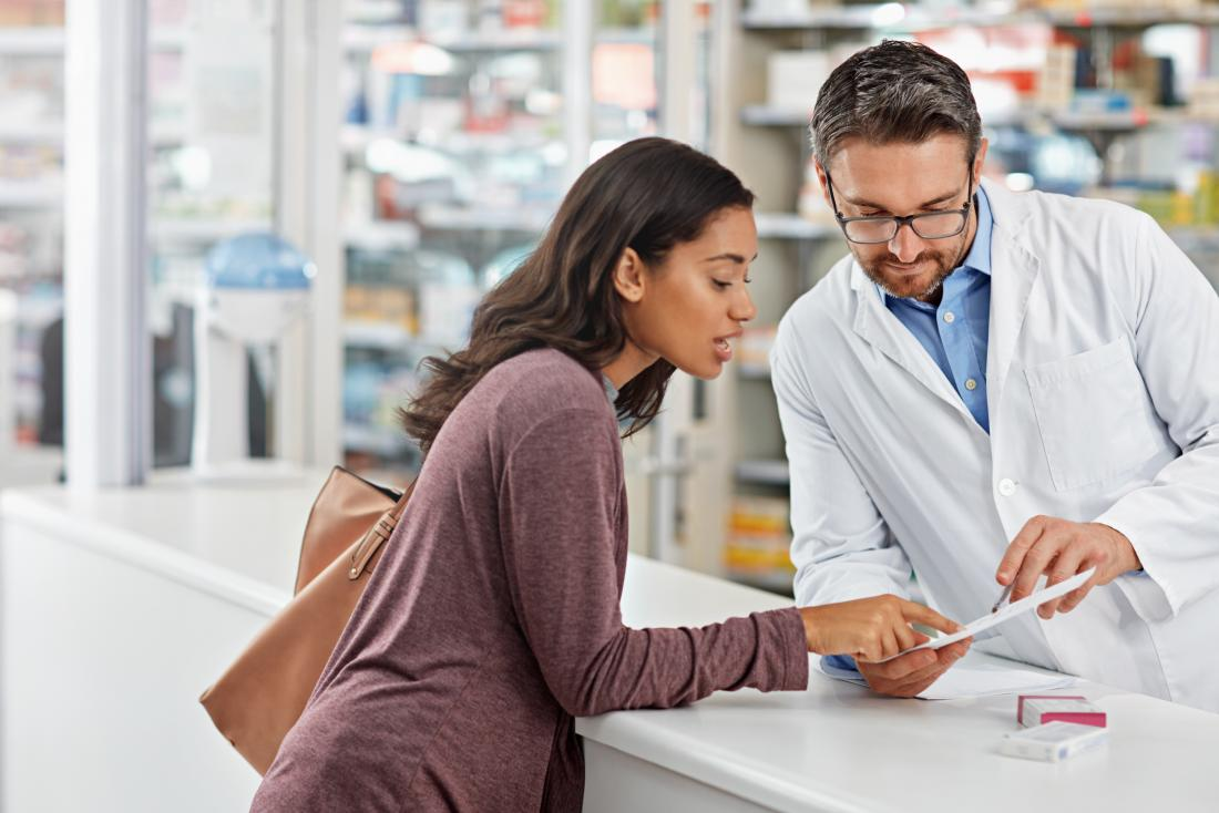 Woman with asthma discusses her nebulizer prescription over counter with pharmacist.