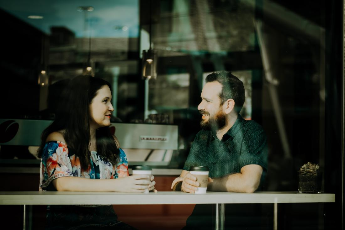 man and woman chatting at a cafe