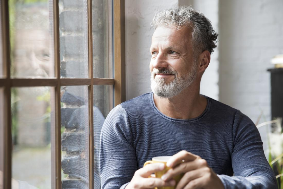man relaxing with coffee by window