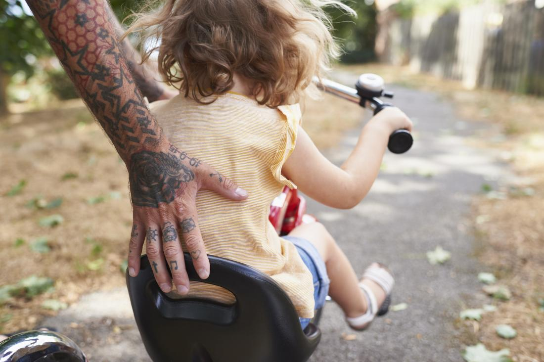 A child on a bike getting pushed along.