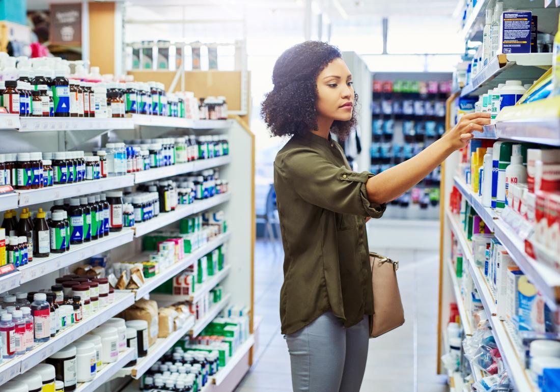 یک زن چیزی را از یک قفسه در یک داروخانه گرفته است.