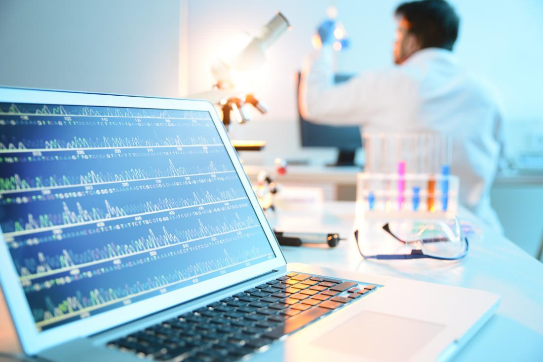 scientist working in lab with DNA structure on a laptop screen