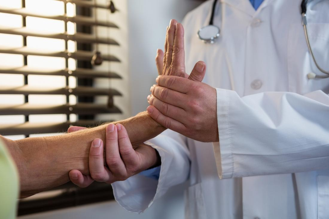 Doctor helping patient with hand and wrist exercises as part of physical therapy