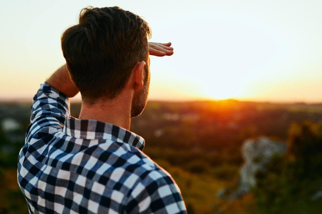 Man looking at a sunset who may have eye floaters