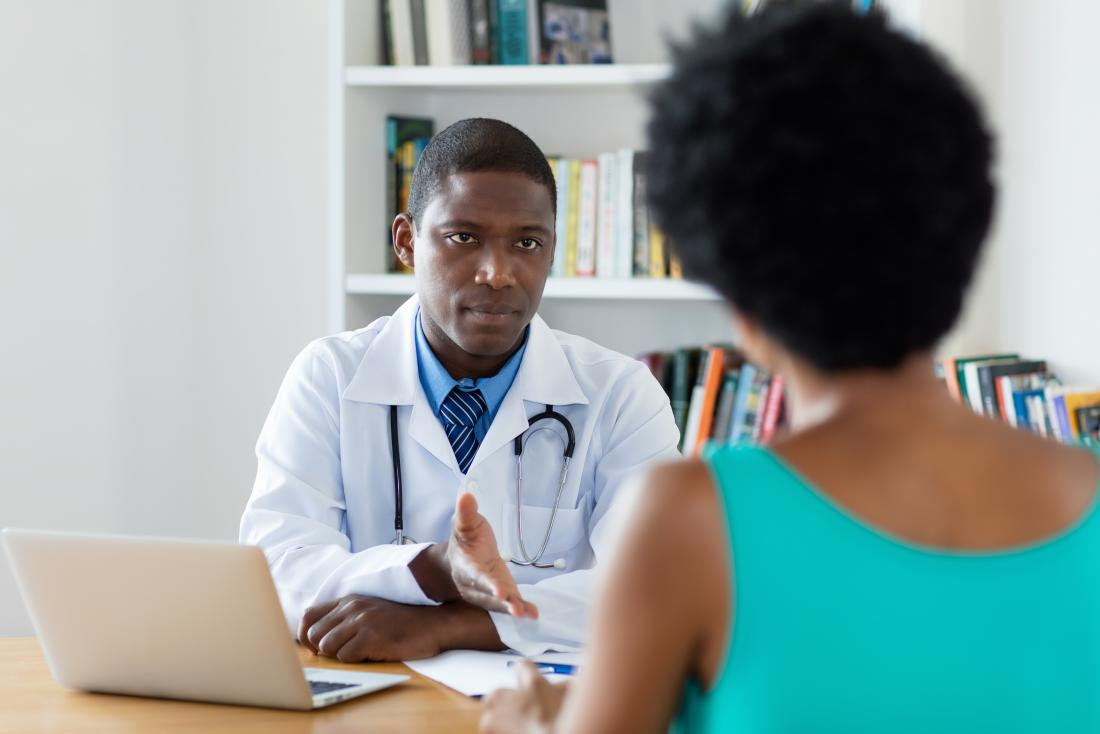 A male doctor talking to a woman in a green top.