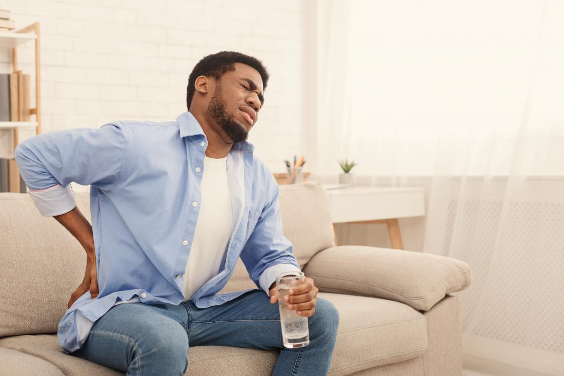 A man sat on the couch with a pain in his lower back.