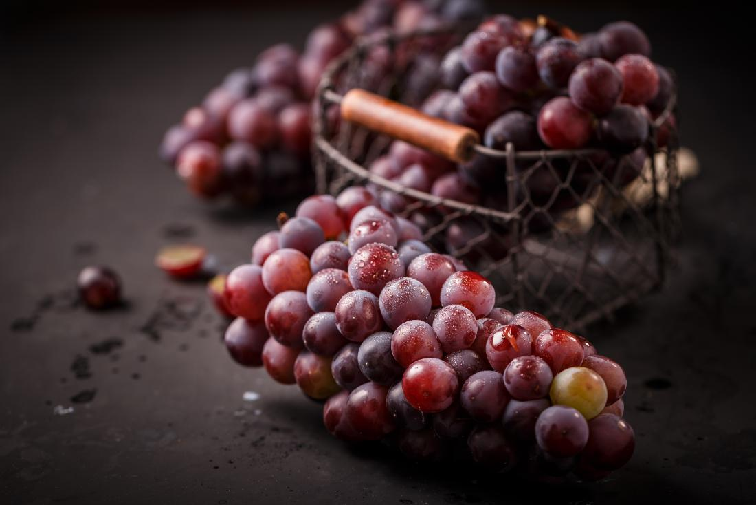 a bunch of grapes on a dark table.