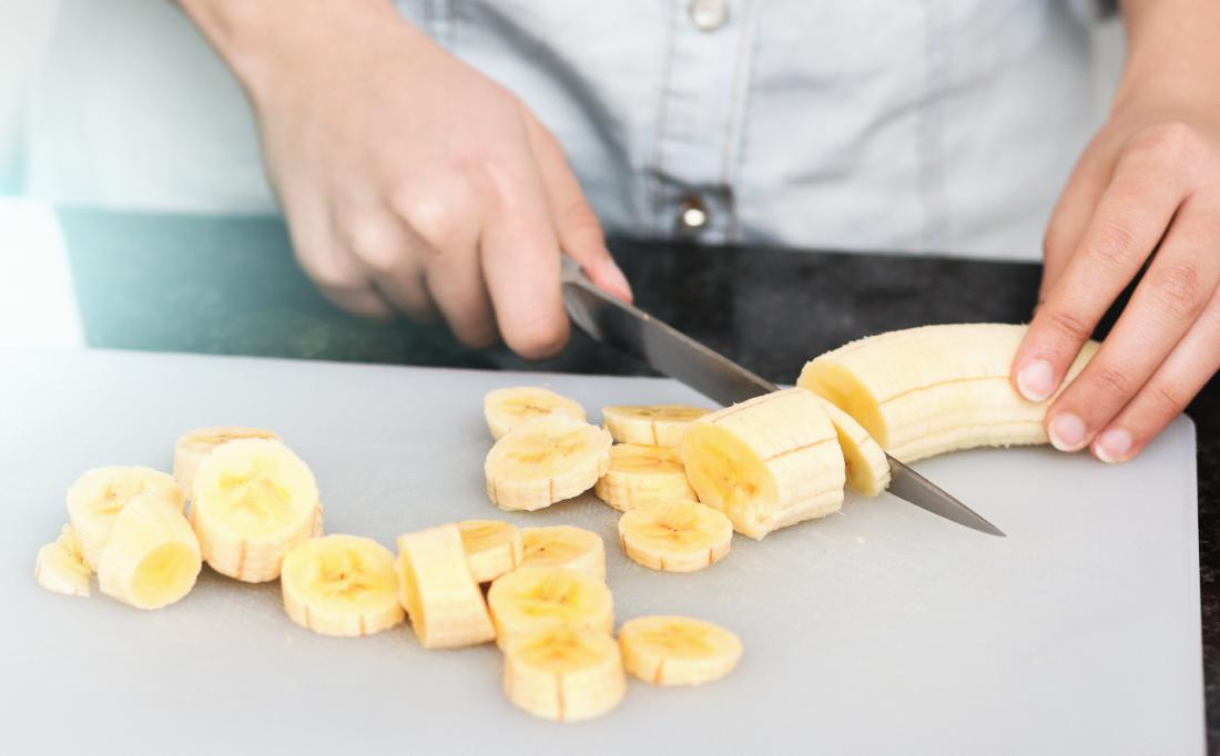 Cutting a banana on a board<!--mce:protected %0A-->