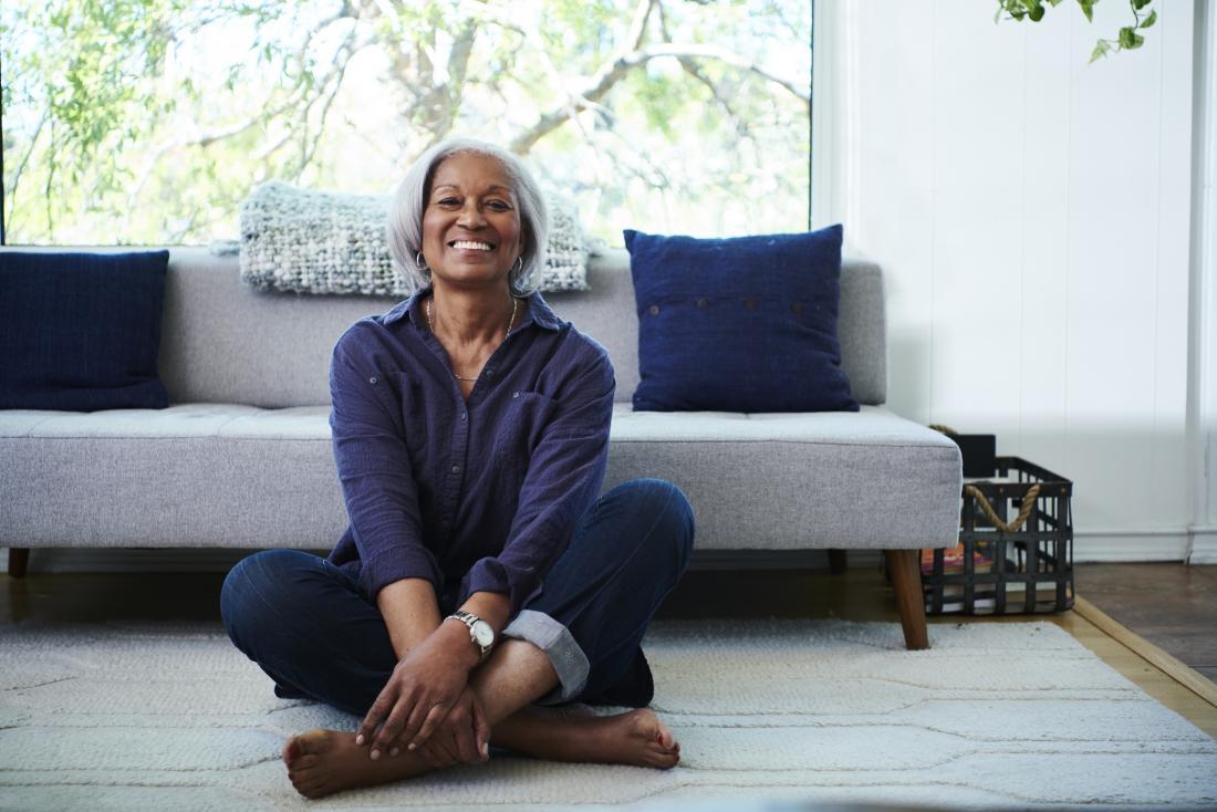 smiling older woman sitting cross legged on the floor