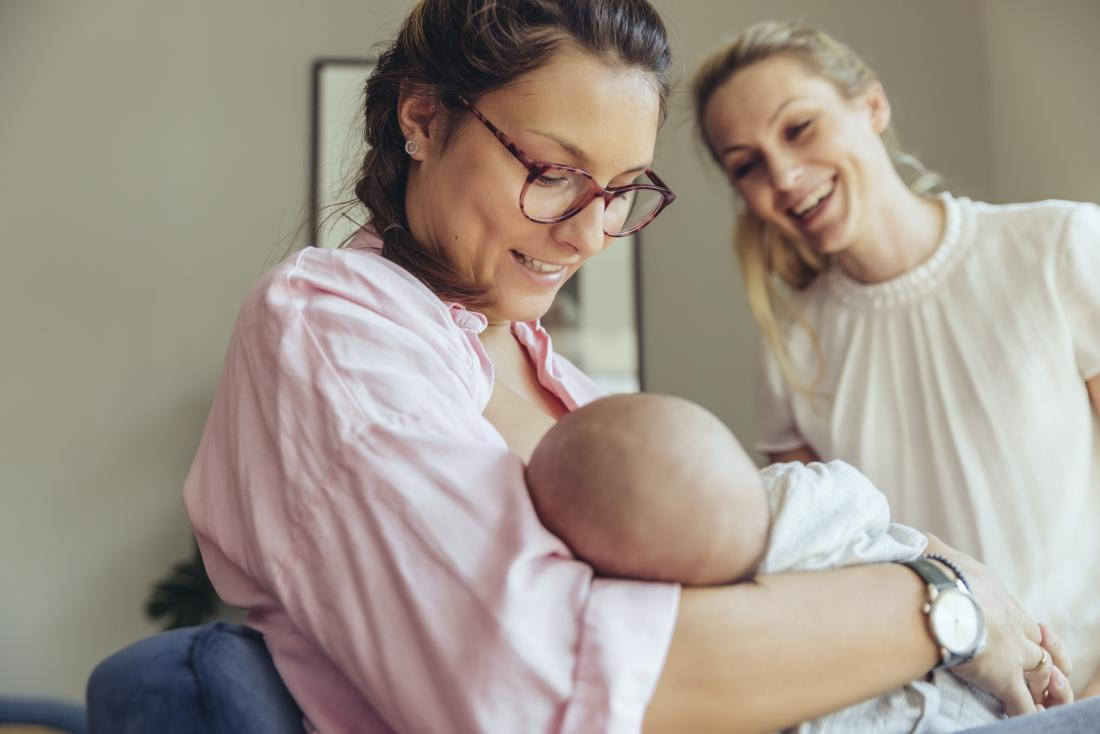 two woman watching their baby breastfeed.