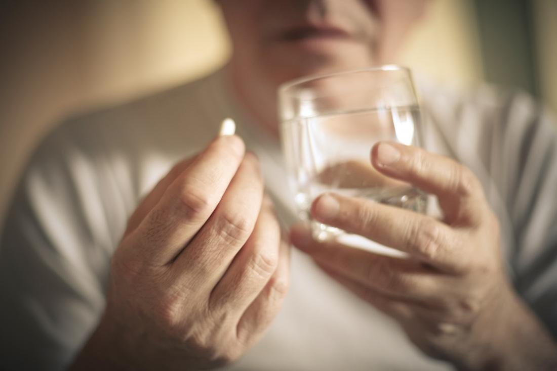 a man about to take a pill with a glass of water.