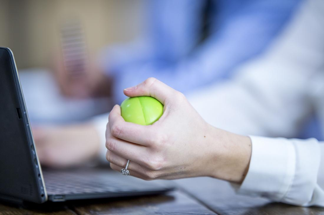 a woman squeezing a stress ball at her desk