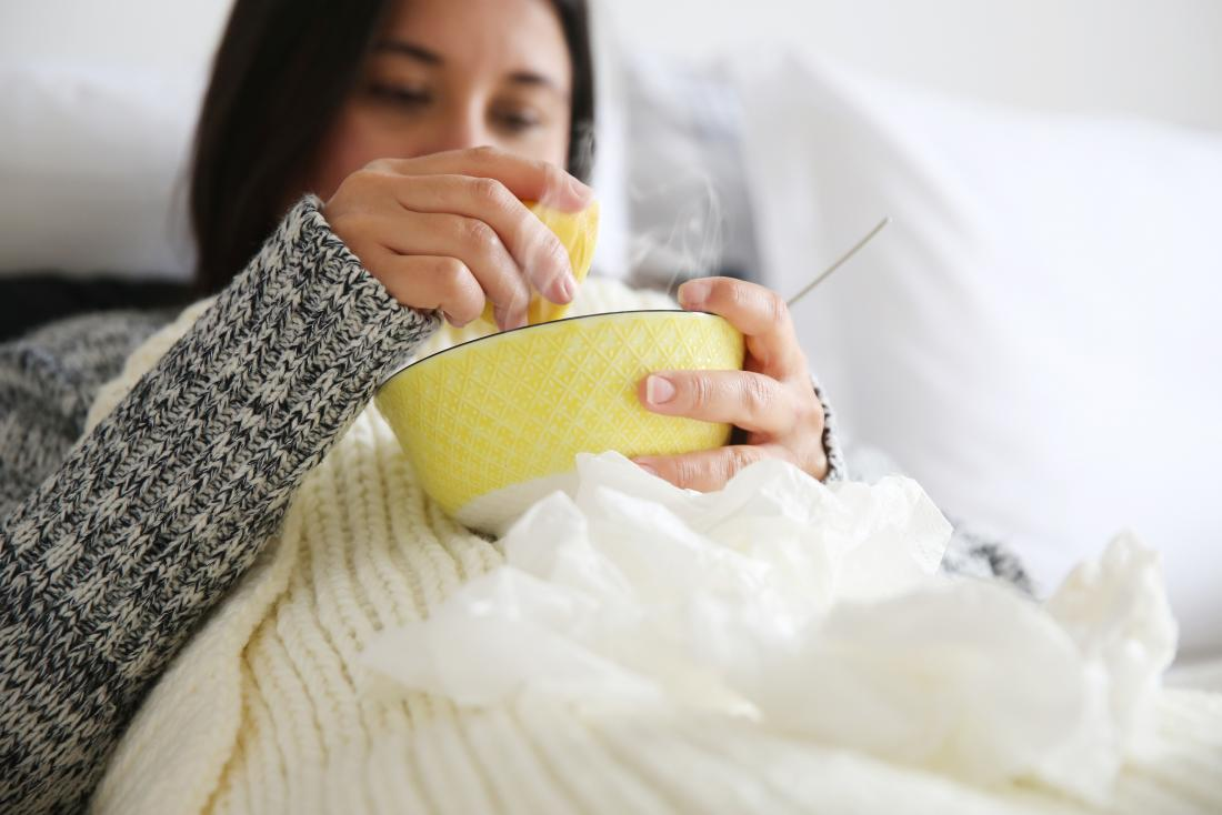 a woman drinking soup as a tonsillitis treatment at home