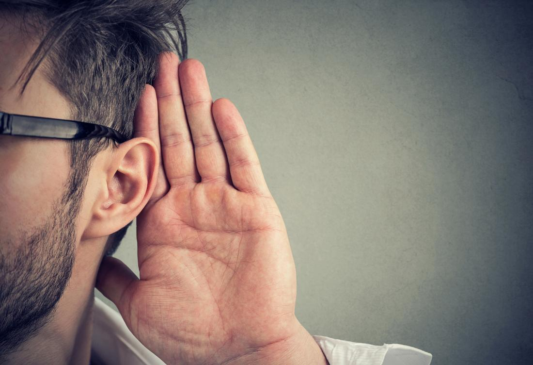 man placing hand next to ear to hear better