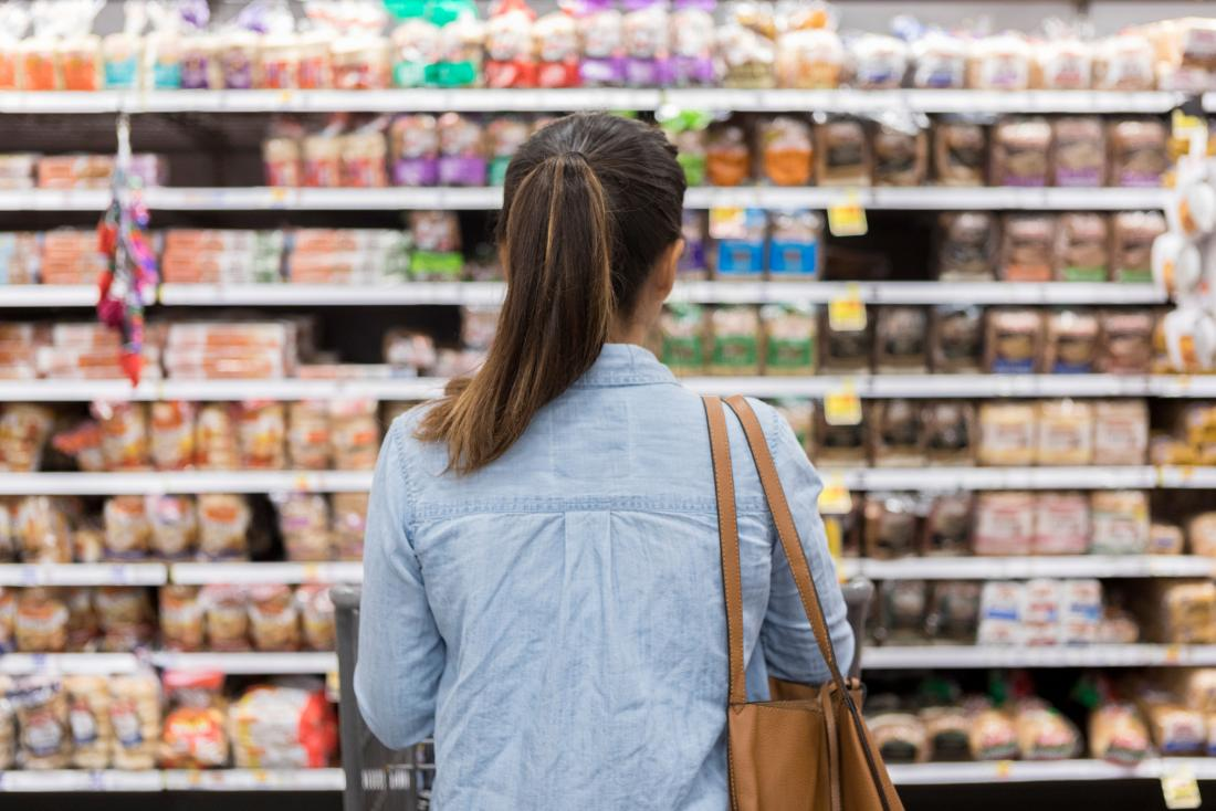 woman looking at processed foods in supermarket aisle seen from behind