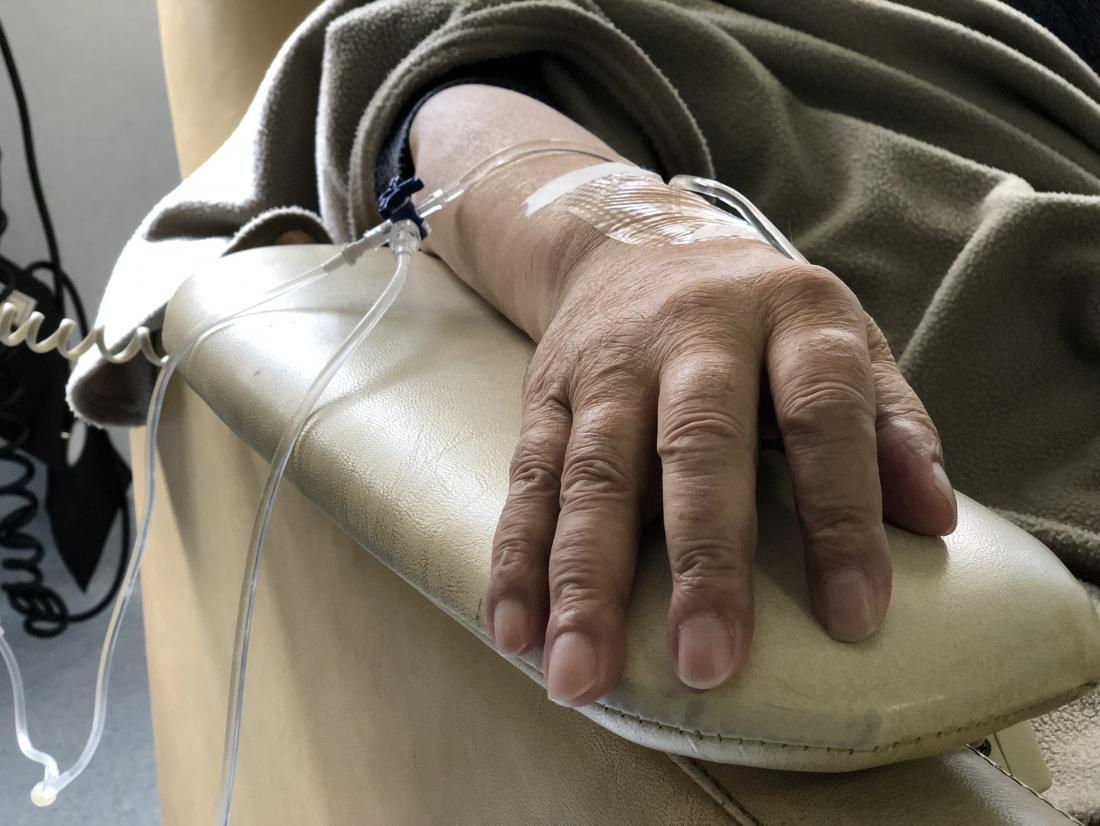 a mans hand who is receiving chemotherapy.