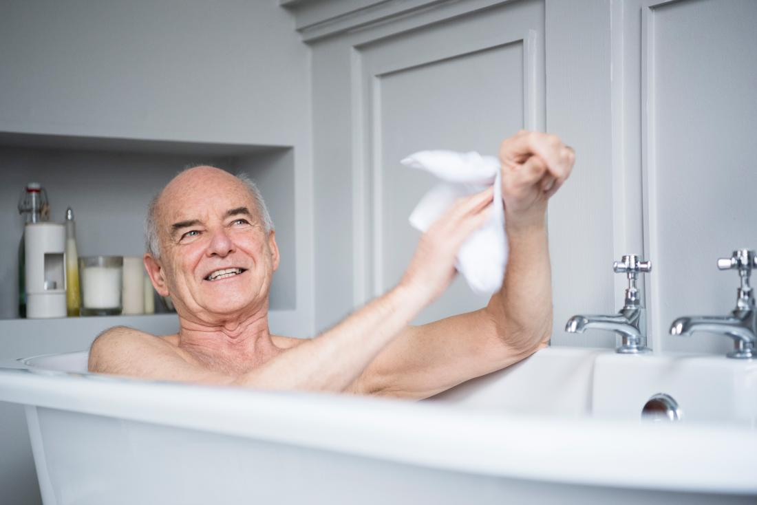 Senior man in bath washing himself whilst smiling