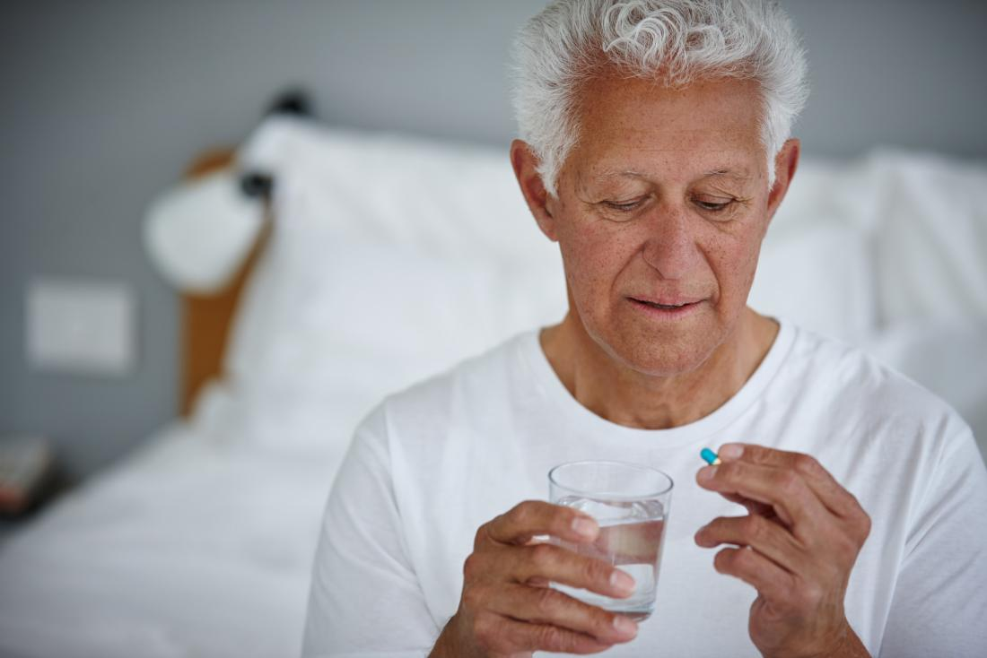 a man taking Doxycycline with a glass of water.