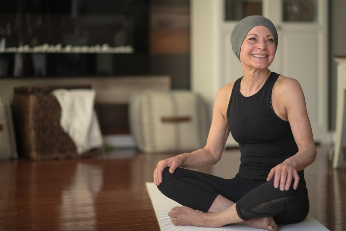 a woman with cancer about to do some yoga.