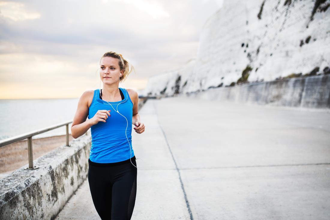 a woman running along aside a cliff side walk.