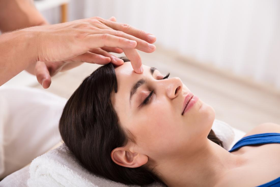 a woman receiving acupressure on the forehead for a headache