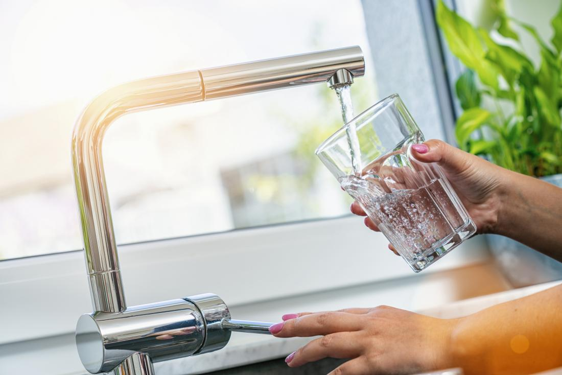 close up of woman's hands pouring tap water